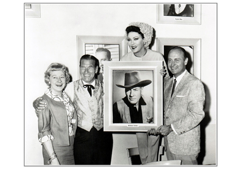 "Linda Darnell helps A.C. welcome Richard Arlen's portrait to his wall of fame at the time of the 1965 production ""Black Spurs."" I'm sorry I don't know the identity of the woman at left."