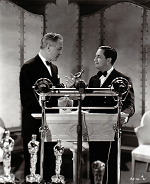 Mervyn LeRoy presents Victor Fleming with his Best Director Oscar for 1939. Note the trio of microphones in front of the podium. One was for the motion picture record of the event, and one was for the assembled guests; it's anyone's guess why there was a third, as this ceremony was not officially broadcast to the public.
