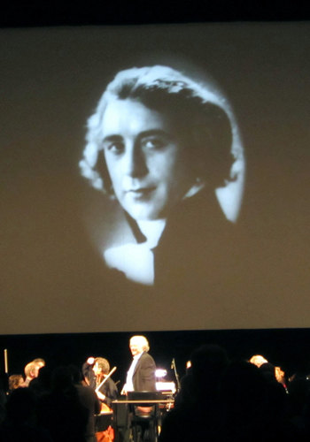 Composer-conductor Carl Davis takes a bow, with the image of Abel Gance (as he appears in his own film, as the character Saint-Just) at the conclusion of 'Napoleon'.