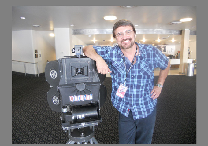Cinerama buff supreme Dave Strohmaier poses with the three-headed camera he used to shoot his new short subject, 'In the Picture'.