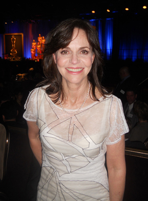 Two-time Academy Award winner Sally Field, a contender again this year, poses with larger-than-life Oscar statues behind her.