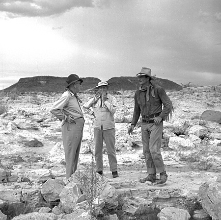 John Ford confers with Hondo director John Farrow and John Wayne on location in Mexico. Ford actually shot some scenes for the film.